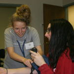 CNA students taking blood pressure