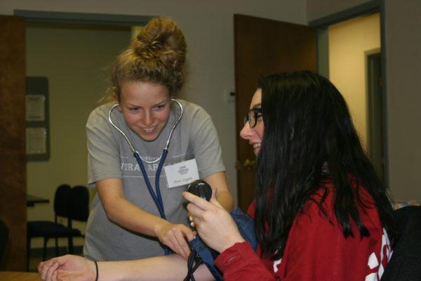 CNA students taking blood pressure